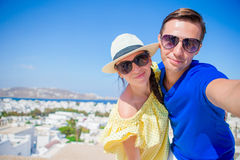 Selfie couple taking pictures at Mykonos island, Cyclades. Tourists people taking travel photos with smartphone on stock photos