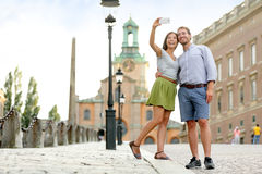 Selfie couple taking pictures at Stockholm palace. Selfie couple taking pictures at Stockholm cathedral and royal palace in Gamla Stan (Old Town) in the capital stock image