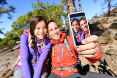 Selfie couple using smart phone hiking in nature Royalty Free Stock Photos