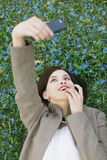 Selfie. Cute woman making selfie lying on the meadow of spring flowers Stock Photography