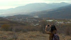 Selfie da jovem mulher durante o por do sol na montanha com video estoque