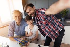 Selfie dans la cuisine Un homme s'est photographié, son père plus âgé et fils Image stock