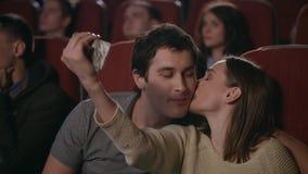 Selfie de baiser dans le cinéma Couples heureux faisant le selfie dans le cinéma clips vidéos