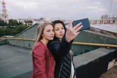 Selfie de deux jeunes filles sur le fond de ville Photographie stock libre de droits