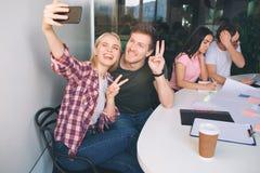 Selfie de fala dos pares novos felizes Sentam-se junto e olham-se a câmera do telefone Os povos mostram o símbolo da parte Uns ou imagem de stock royalty free