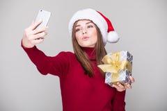 Selfie de la toma de la mujer en el teléfono con el sombrero de la Navidad Imagen de archivo