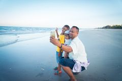 Selfie de papa et de fils à la plage Image stock