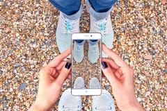 Selfie de pies y del teléfono elegante en la playa foto de archivo