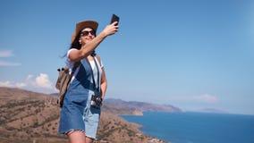 Selfie de prise femelle de touristes de sourire de femme heureuse au fond de paysage marin de montagne clips vidéos