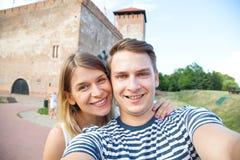 Selfie de sourire de couples devant le château historique Images libres de droits