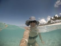 Selfie de un centro sonriente envejeció la mujer en sombrero y sombras en el mar a fotografía de archivo libre de regalías