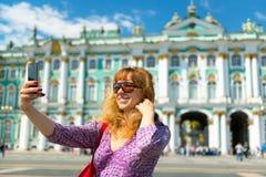 Selfie de un turista femenino joven cerca del palacio del invierno en santo Fotos de archivo libres de regalías