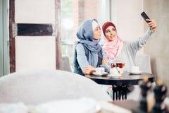Selfie del amigo de la mujer de dos musulmanes por smartphone Imágenes de archivo libres de regalías