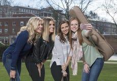 Selfie del gruppo - 4 belle donne sulla città universitaria dell'istituto universitario Immagine Stock Libera da Diritti