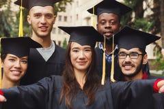 Selfie del gruppo degli studenti che celebrano graduazione Immagine Stock