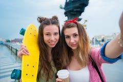 Selfie del makihg de dos muchachas del inconformista con el monopatín al aire libre en luz de la puesta del sol Mujeres deportiva Imagen de archivo
