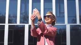 Selfie delante de los rascacielos ultra modernos Retrato de la vista lateral Juventud de oro almacen de video