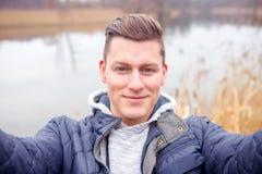 Selfie dell'uomo biondo bello davanti al lago Immagini Stock