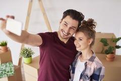 Selfie delle coppie sorridenti nella loro nuova casa fotografie stock