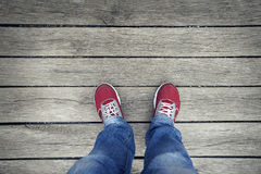 Selfie des espadrilles rouges sur des jambes sur un fond en bois Photos stock