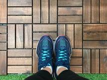 Selfie des pieds avec des chaussures d'espadrille sur le plancher en bois de tuile et d'herbe Photographie stock