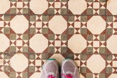 Selfie des pieds avec des chaussures d'espadrille sur le plancher de tuiles de modèle d'art, vue supérieure Images stock
