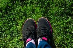 Selfie des pieds femelles sur les espadrilles noires se tenant sur l'herbe verte Photos stock
