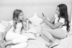 Selfie di modellistica dei bambini - due bambine che fanno selfie sullo smartphone bambini delle bambine che modellano nella came immagini stock
