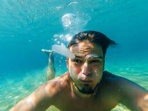 Selfie di un uomo con un fronte sorpreso divertente sotto acqua e le meduse Fotografia Stock Libera da Diritti