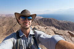 Selfie di viaggiatore con zaino e sacco a pelo del cowboy sulla montagna sopra la città di Eilat del Mar Rosso immagine stock