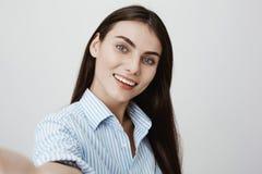 Selfie die van jong en aantrekkelijk vrouwelijk model, ruim en geluk glimlachen uitdrukken terwijl het houden van camera over gri royalty-vrije stock foto