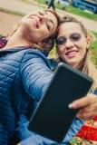 Selfie divertido de dos amigos hermosos en una tableta Fotografía de archivo libre de regalías