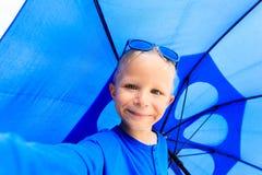 Selfie do rapaz pequeno com o guarda-chuva no verão chuvoso Fotografia de Stock