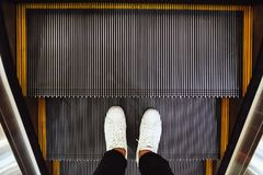 Selfie dos pés do homem nas sapatas brancas da sapatilha em etapas de escada rolante na opinião superior do shopping no estilo do imagem de stock royalty free