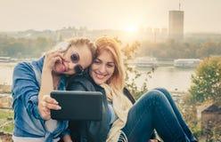 Selfie drôle de deux beaux amis sur un comprimé Image stock