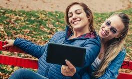 Selfie drôle de deux beaux amis sur un comprimé Photo stock