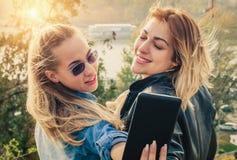 Selfie drôle de deux beaux amis sur un comprimé Photographie stock libre de droits