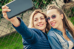 Selfie drôle de deux beaux amis sur un comprimé Photographie stock