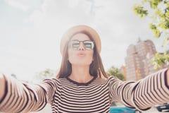 Selfie e um beijo do ar! A senhora bonito nova é fotografar exterior fotos de stock royalty free
