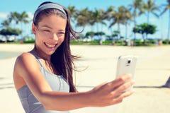 Selfie-Eignungsfrau auf Strand mit Smartphonezelle Stockfotos
