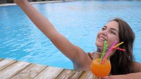 Selfie en hembra sonriente de las vacaciones fotografió en el teléfono móvil en piscina en centro turístico costoso almacen de metraje de vídeo