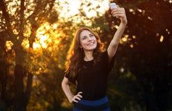 Selfie facente abbastanza castana dei giovani in Prak sul fondo della natura fotografia stock libera da diritti