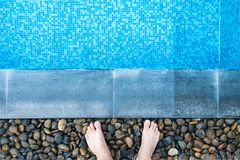 Selfie the feet at the pool side or edge with blue mosaic tiles. At the bottom of the swimming pool Stock Photography