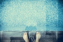 Selfie the feet at the pool side or edge with blue mosaic tiles. At the bottom of the swimming pool. vintage tone Royalty Free Stock Photo