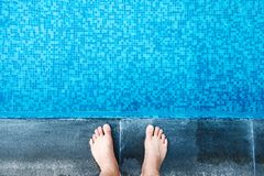 Selfie the feet at the pool side or edge with blue mosaic tiles. At the bottom of the swimming pool Stock Photo
