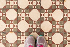 Selfie of feet with sneaker shoes on art pattern tiles floor, top view Stock Images