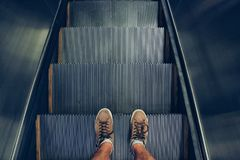 Selfie of feet in sneaker shoes on escalator steps in vintage style. Selfie of feet in sneaker shoes on escalator steps, top view in vintage style Stock Image