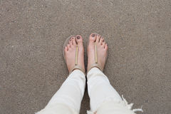 Selfie Feet Wearing Gold Sandals and White Jeans on Ground Background Royalty Free Stock Images