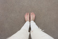 Selfie Feet Wearing Gold Sandals and White Jeans on Ground Background Royalty Free Stock Photography