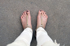 Selfie Feet Wearing Gold Sandals and White Jeans on Ground Background Stock Image